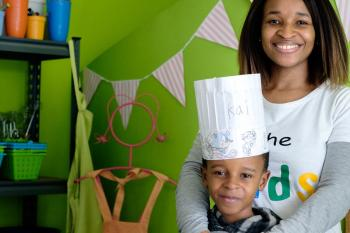 A woman stands in a kitchen with a boy wearing a chef's hat